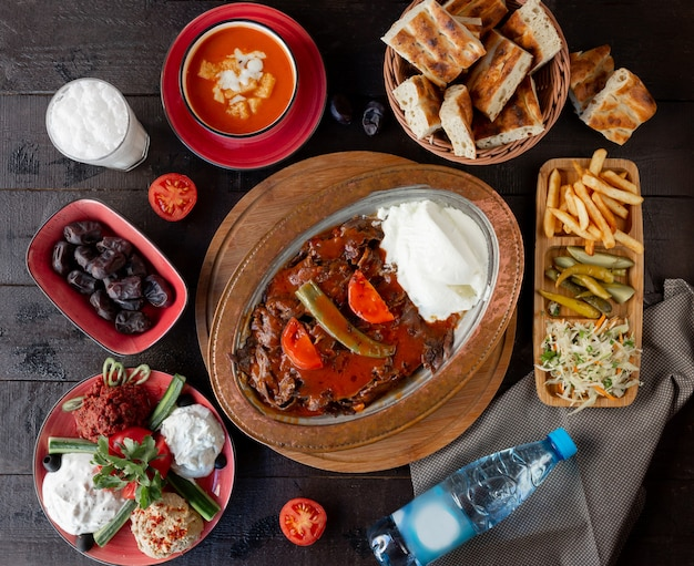 Top view of lunch setup with iskender kebab, tomato soup, pickles, turkish meze Free Photo