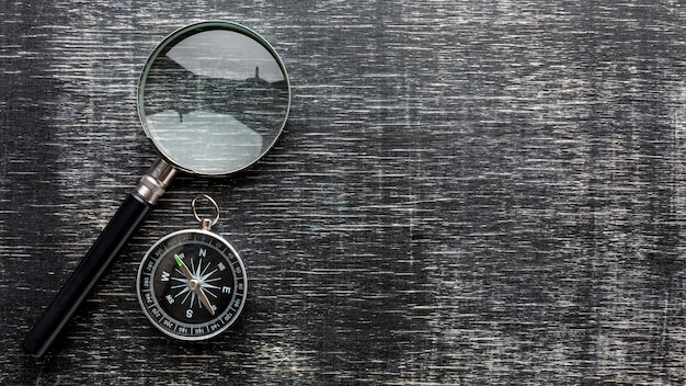 Top view magnifying glass and compass Free Photo