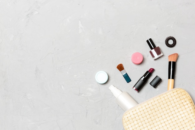 Top view of make up products fallen out of cosmetics bag on cement Premium Photo