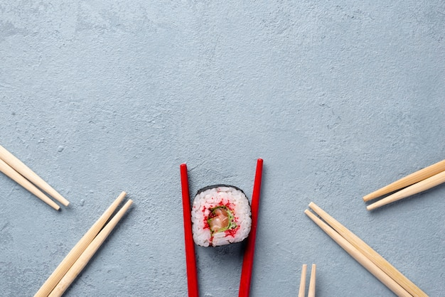Top view maki sushi roll and chopsticks with copy space Free Photo