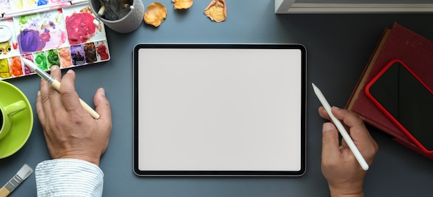 Top view of male artist working on his project on blank screen tablet in his creative studio Premium Photo