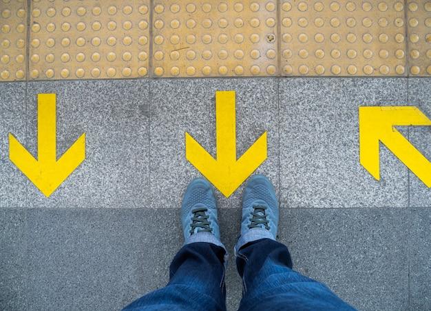 Top view of man feet standing over arrow symbol on subway platform. Premium Photo
