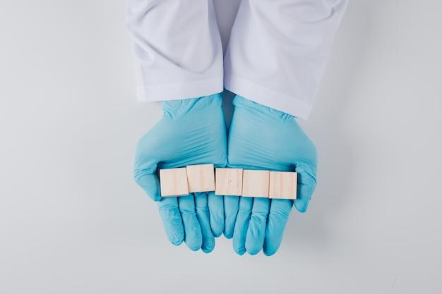 Uomo di vista superiore in guanti che tengono i blocchi di legno in entrambe le mani su bianco Foto Gratuite