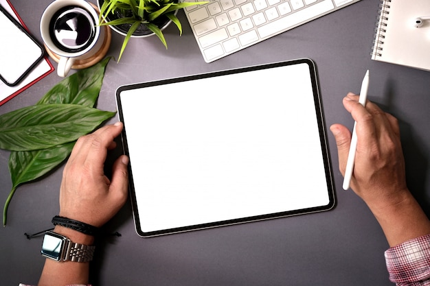 Top view man holding blank screen tablet on  home workspace desk Premium Photo