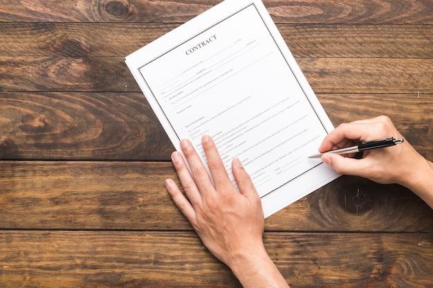 Человек взгляд сверху подписывая контракт на деревянном столе Premium Фотографии