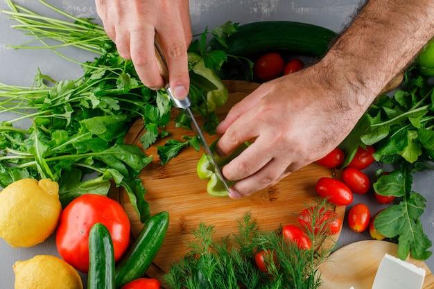 灰色の表面にトマト、塩、チーズ、レモンとまな板の上のピーマンをスライスするトップビュー男 無料写真