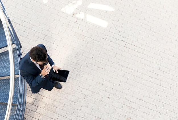 Top view man with tablet drinking coffee Free Photo
