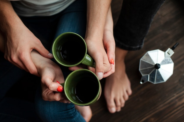 Top view man and woman holding cups with coffee Free Photo