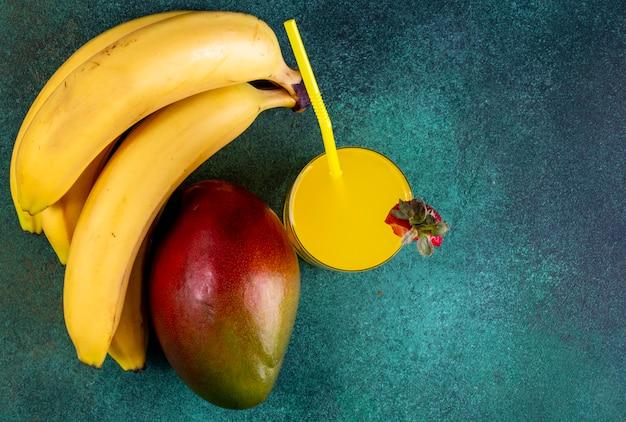 Вид сверху манго с бананами и апельсиновым соком с желтой соломкой на зеленом Бесплатные Фотографии