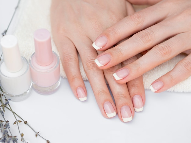 Top view manicured hands and nail polish Free Photo