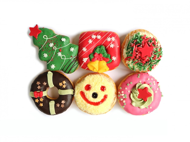 Top view of many colorful christmas decorated doughnuts sweets isolated on white background Premium Photo