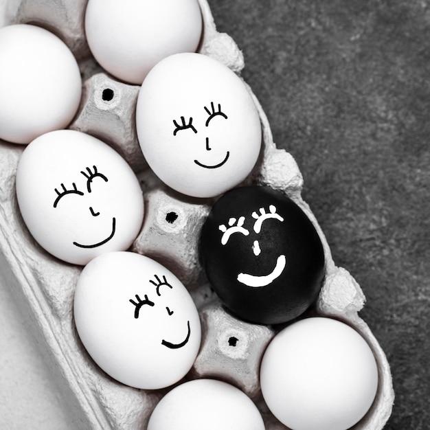 Vista dall'alto di molte uova colorate diverse con facce per il movimento della materia delle vite nere Foto Gratuite