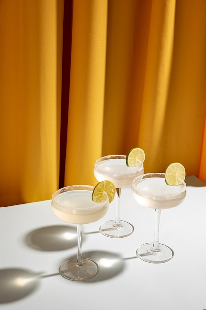 Top view of margarita cocktail glasses with salty rim and lime on white table Free Photo