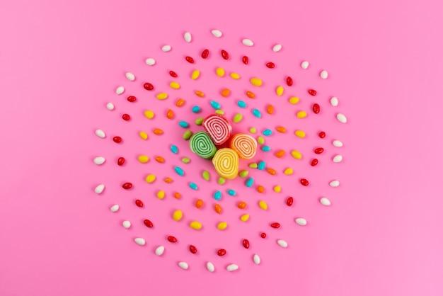 Una marmellata di arance con vista dall'alto e caramelle colorate che formano un cerchio sul colore rosa, zucchero dolce Foto Gratuite