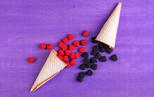 ラズベリーと紫色の背景にワッフルコーンとブラックベリーの形でトップビューマーマレード 無料写真