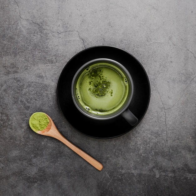 Top view of matcha tea in cup with spoon Free Photo