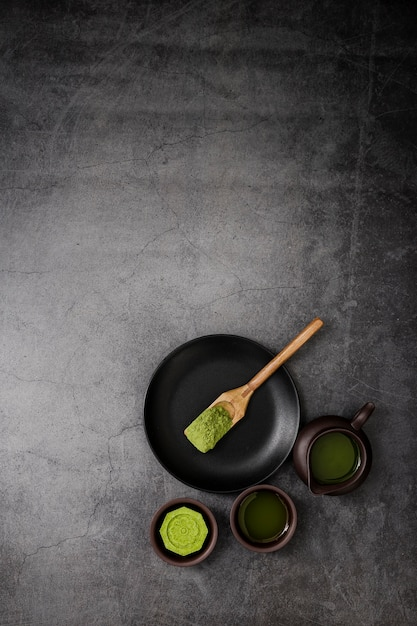 Top view of matcha tea cup with wooden scoop on plate Free Photo