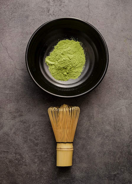 Top view of matcha tea powder in bowl with bamboo whisk Free Photo