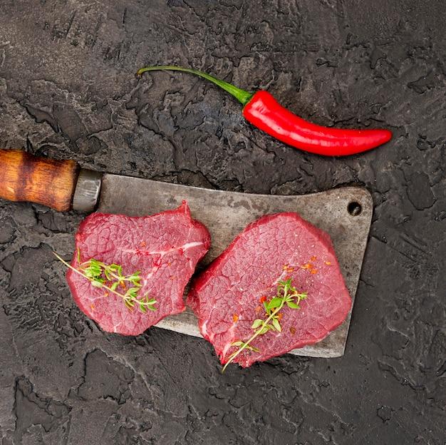 Vista dall'alto di carne su mannaia con erbe e peperoncino Foto Gratuite