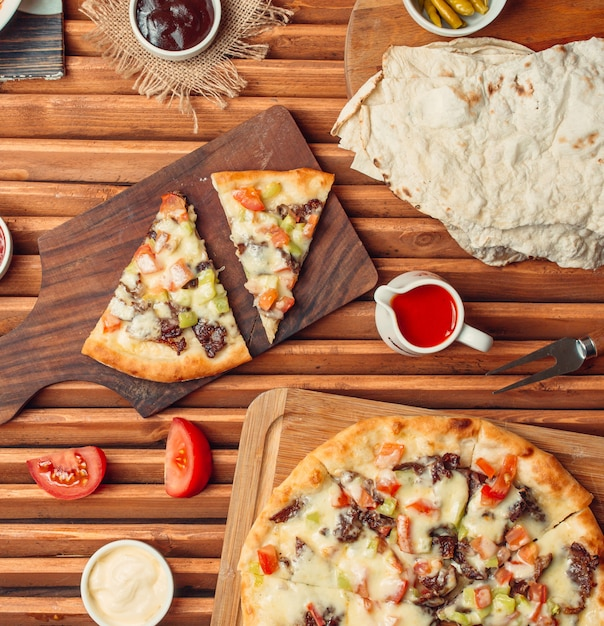 Top view of meat pizza slices on wood cutting board Free Photo