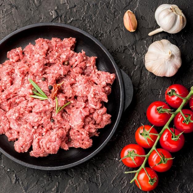 Vista dall'alto di carne sul piatto con aglio e pomodori Foto Gratuite