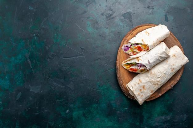 Вид сверху мясной сэндвич сэндвич из мяса, приготовленного на вертеле, нарезанный на синем столе сэндвич бургер еда обед мясо фото Бесплатные Фотографии