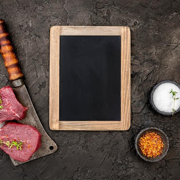 Vista dall'alto di carne con mannaia e lavagna Foto Gratuite