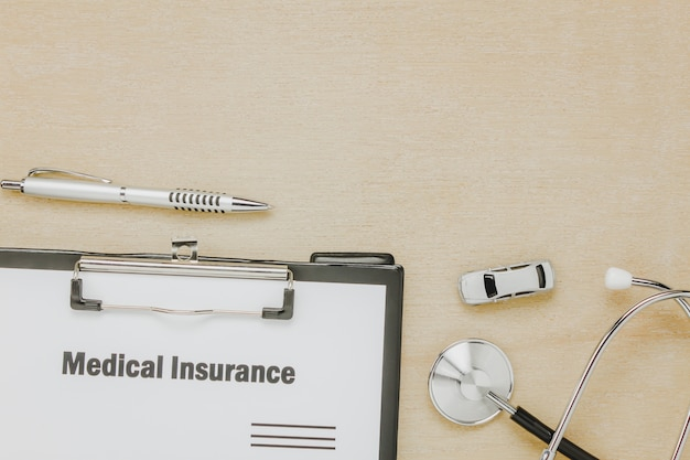 Top view medical insurance form with stethoscope,car on wooden background. Free Photo