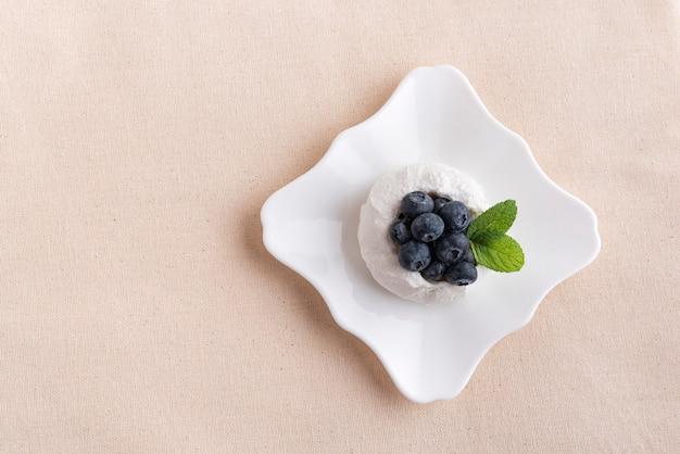 Торт безе вида сверху со свежей черникой на поддоннике. Premium Фотографии