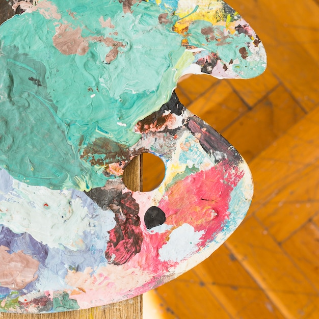 Top view of messy oil paint wooden palette Free Photo