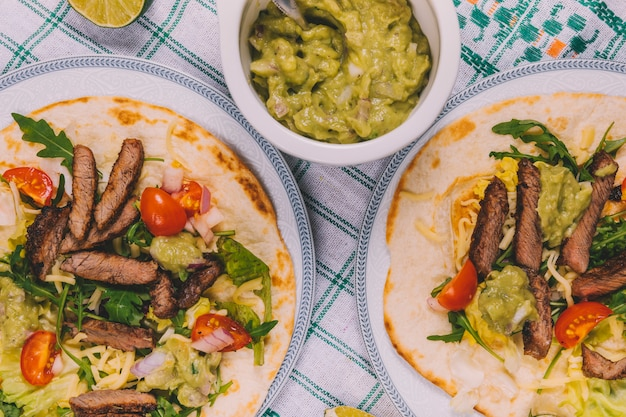 Top view of mexican beef stripes in tortilla with bowl of guacamole over table cloth Free Photo