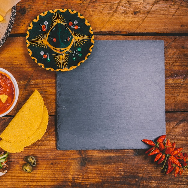 Top view of mexican hat; salsa sauce; tortilla; black slate and red chilies over wooden bench Free Photo