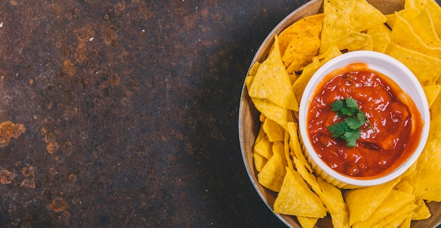 Top view of mexican nachos chips with spicy salsa sauce in bowl Free Photo