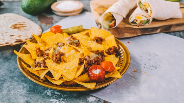 Top view of mexican nachos tortilla chips in bowl with mexican tacos on cutting board Free Photo