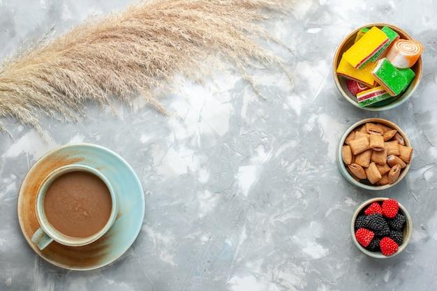 Вид сверху молочный кофе с конфетами, печенье и ягодные конфитюры на белом фоне пить конфеты сладкий сахар Бесплатные Фотографии