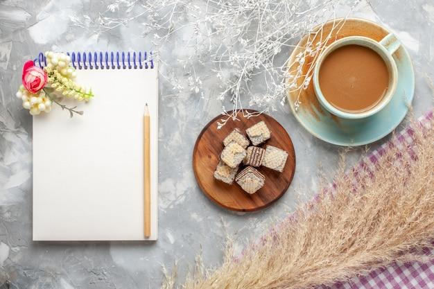 明るい背景のチョコレートワッフルとメモ帳とトップビューミルクコーヒーチョコレートクッキー甘い砂糖 無料写真