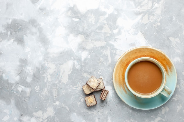 Vista dall'alto caffè al latte con cialde sul colore del latte cialda zucchero dolce scrivania luce Foto Gratuite