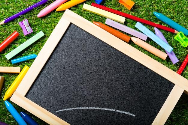 Top view of mini blackboard and colors on plastic grass Premium Photo