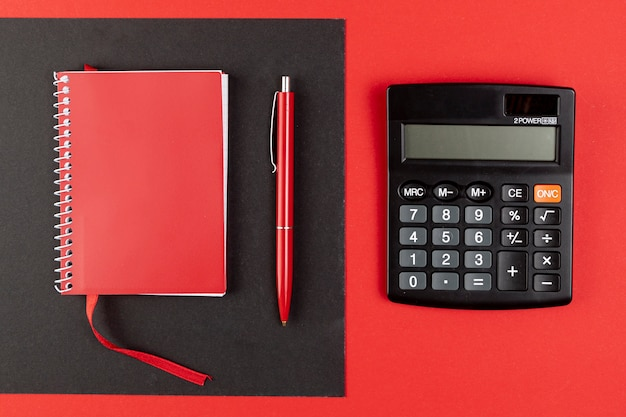 Top view mini calculator next to red notebook Free Photo