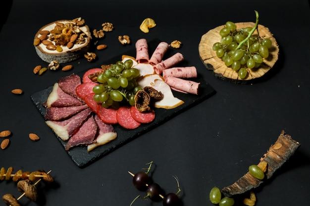 黒いテーブルの上のドライフルーツとスタンドのブドウとナッツのトップビューmisnayaプレート 無料写真