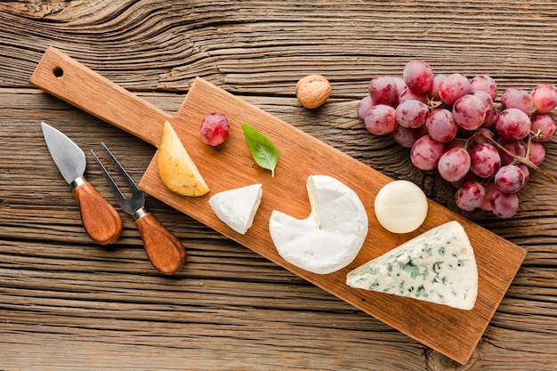 Top view mix of gourmet cheese on wooden cutting board with grapes and ustensils Free Photo