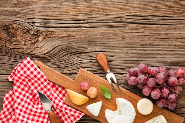 Top view mix of gourmet cheese on wooden cutting board with grapes Free Photo