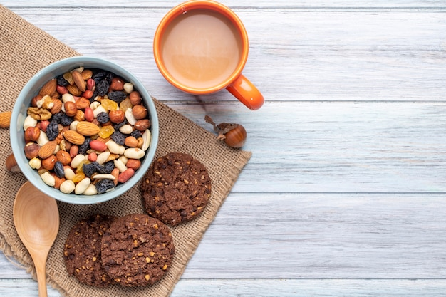 Top view of mix of nuts and dried fruits in a bowl and oatmeal cookies with a mug of cocoa drink on rustic Free Photo