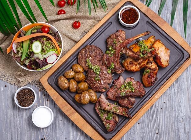 Вид сверху микс стейков с картофельным овощным салатом и соусом Бесплатные Фотографии