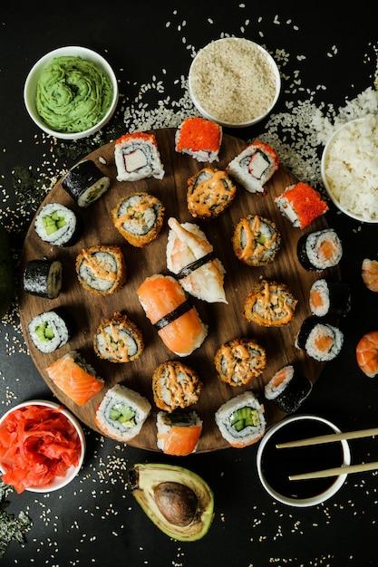 Rotoli di mix vista dall'alto su un supporto con salsa di soia wasabi zenzero avocado e semi di sesamo Foto Gratuite
