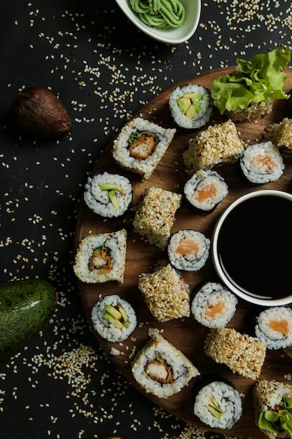 Vista dall'alto mescolare rotoli con salsa di soia su un supporto con semi di sesamo avocado riso allo zenzero e wasabi Foto Gratuite
