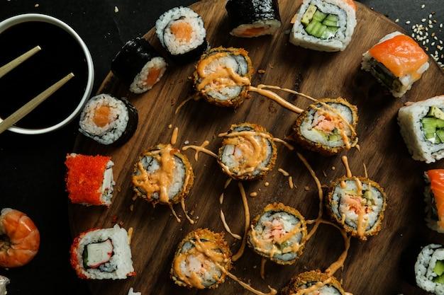 屋台で生姜醤油わさびごまとアボカドを組み合わせた巻き寿司のトップビュー 無料写真