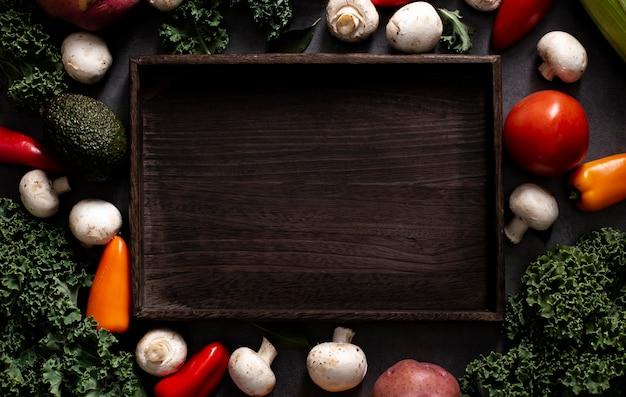 Vista dall'alto mix di verdure con vassoio in legno vuoto Foto Gratuite