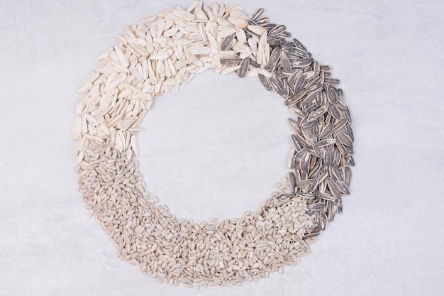 Vista dall'alto di semi di girasole misti sulla superficie bianca. Foto Gratuite