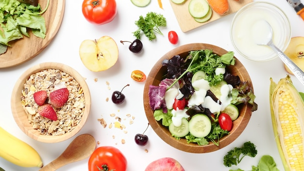 Top view of mixed vegetables salad, muesli and fresh fruits on white background. Premium Photo